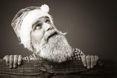 Hübscher junger Mann mit gefrorenem Bart und Sankt bedecken oben schauen mit einer Kappe Stockfoto