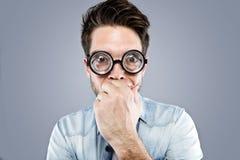Hübscher junger Mann mit lustigen Gläsern scherzend und lustiges Gesicht über grauem Hintergrund machend Stockbild