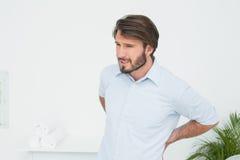 Hübscher junger Mann mit Rückenschmerzen stockfoto