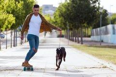 Hübscher junger Mann mit seinem Hund, der in den Park Skateboard fährt Lizenzfreie Stockfotografie