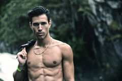 Hübscher junger Mann nahe Gebirgswasserfall mit Hemd auf Schulter Lizenzfreies Stockbild