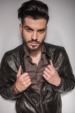 Hübscher junger Modemann, der seine Jacke zieht Stockfotos