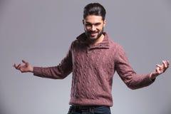 Hübscher junger Modemann, der Sie begrüßt Stockfotografie