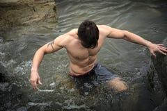 Hübscher junger Muskelmann, der im Wasserteich, nackt steht Lizenzfreie Stockbilder