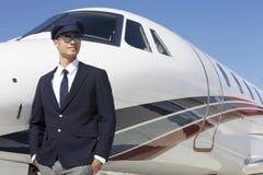 Hübscher junger Pilot, der privates Flugzeug bereitsteht Stockbild