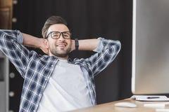 hübscher junger Programmierer in den Brillen lächelnd an der Kamera beim Sitzen mit den Händen hinter Kopf lizenzfreie stockfotografie