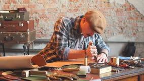 Hübscher junger Schuster, der Leder in der Werkstatt mit speziellem Messer schneidet stock footage