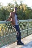 Hübscher junger schwarzer Mann lehnt sich auf dem Geländer einer Brücke Stockbild