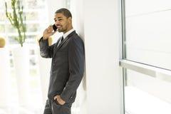 Hübscher junger schwarzer Mann mit Handy Stockbild