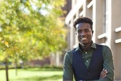 Hübscher junger schwarzer Studentenmann lächelt, stehend auf colege campu Lizenzfreies Stockfoto