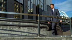 Hübscher junger selbstbestimmter Bürovorsteher, der geht zu arbeiten, Gebäudekarriere lizenzfreie stockfotos