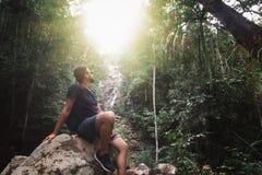 Hübscher junger stilvoller Mann im schwarzen T-Shirt und in der Sonnenbrille nimmt an Trekking im grünen Dschungel teil lizenzfreie stockbilder