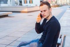 Hübscher junger Student, der Handy verwendet. Stockfoto