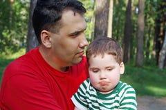 Hübscher junger Vater mit kleinem nettem Sohn sitzen Lizenzfreie Stockfotografie