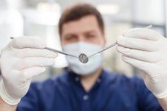Hübscher junger zahnmedizinischer Doktor bereitet sich für Arbeit vor Lizenzfreie Stockbilder