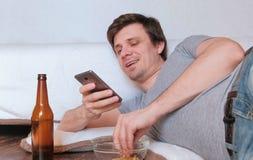 Hübscher Junggeselle des jungen Mannes, der Chips isst und Bier und seinen Handy grasend trinkt stockfotografie