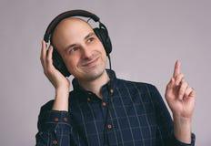 Hübscher kahler Mann, der die Musik genießt Stockfotos