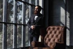 Hübscher kaukasischer Geschäftsmann kleidete in der Klage nahe dem Fenster im Dachbodeninnenraumstudio an stockbilder