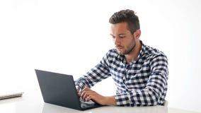 Hübscher kaukasischer Mann, der auf Laptop und dem Lächeln schreibt stock video