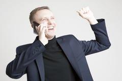 Hübscher kaukasischer Mann in elegantem Siut, das unter Verwendung des Handys spricht Stockfotografie