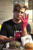 Hübscher kaukasischer Mann setzt sich auf schützende rosa Handschuhe lizenzfreies stockbild