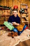 Hübscher Kerl öffnet ein Geschenk im Raum mit Weihnachtsdekorationen Stockfotos