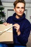 Hübscher Kerl öffnet ein Geschenk im Raum nahe dem Weihnachtsbaum n Lizenzfreie Stockbilder