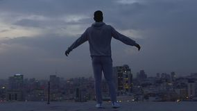 Hübscher Kerl, der auf Dachkante, glaubend überzeugt und frei meditiert stock video