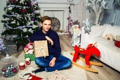 Hübscher Kerl, der ein Geschenk im Raum nahe dem Weihnachten tr hält Lizenzfreies Stockbild