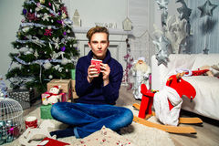 Hübscher Kerl, der eine Schale in einem Raum nahe einem Weihnachtsbaum hält neu Lizenzfreie Stockbilder