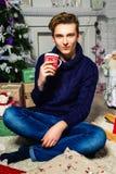 Hübscher Kerl, der eine Schale in einem Raum nahe einem Weihnachtsbaum hält neu Lizenzfreie Stockfotos