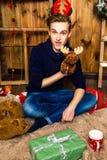 Hübscher Kerl, der einen Spielzeugelch im Raum mit Weihnachten-deco hält Stockfotografie