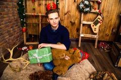 Hübscher Kerl, der mit einem Geschenk im Raum mit Weihnachten-deco sitzt Stockfotos