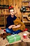 Hübscher Kerl, der mit einem Spielzeugbären im Raum mit Weihnachten sitzt Stockbild