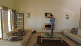 Hübscher Kerl, der am Telefon im Wohnzimmer spricht stock video footage