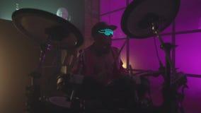 Hübscher Kerl hinter der Trommelausrüstung im Hemd und in der Hose ablage Mann im Raum, der die Trommeln spielt stock footage