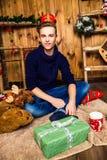 Hübscher Kerl ist er, lächelnd sitzend und in einem Raum mit Weihnachten Lizenzfreies Stockfoto