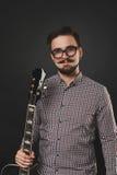 Hübscher Kerl mit dem Bart, der Akustikgitarre hält Lizenzfreies Stockfoto