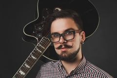 Hübscher Kerl mit dem Bart, der Akustikgitarre hält Lizenzfreies Stockbild