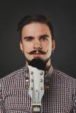 Hübscher Kerl mit dem Bart, der Akustikgitarre hält Stockfoto