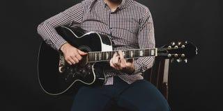 Hübscher Kerl mit dem Bart, der Akustikgitarre hält Stockfotografie