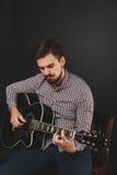 Hübscher Kerl mit dem Bart, der Akustikgitarre hält Lizenzfreie Stockfotos