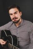 Hübscher Kerl mit dem Bart, der Akustikgitarre hält Lizenzfreie Stockfotografie