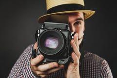Hübscher Kerl mit dem Bart, der Weinlesekamera hält Stockfotografie