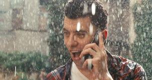 Hübscher Kerl mit dem schwarzen Haar spricht emotional am Handy und glücklich schreit und hebt Hände oben herein an stock video footage