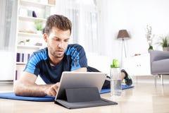Hübscher Kerl mit dem Tablet-Computer, der auf einer Matte liegt Lizenzfreie Stockfotos
