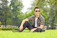 Hübscher Kerl mit der Sonnenbrille, die auf Gras sitzt und Nocken betrachtet Lizenzfreie Stockfotos