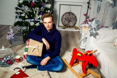 Hübscher Kerl mit einem Geschenk im Raum nahe dem Weihnachtsbaum Ne Stockbild