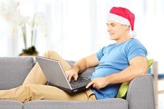 Hübscher Kerl mit Sankt-Hut auf einem Sofa, das an einem Laptop am hom arbeitet Stockfotografie