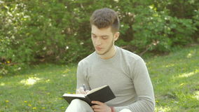 Hübscher Kerl sitzt auf einem Gras am Park und macht Anmerkungen im Buch stock video